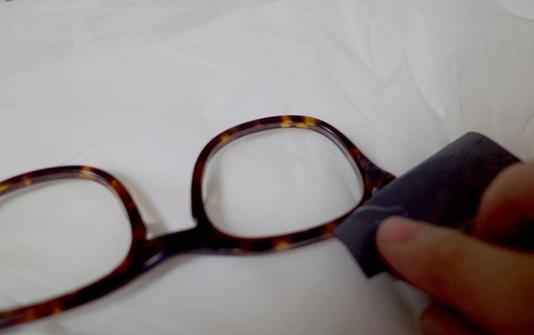 白く汚れたメガネフレームを耐水ペーパーで磨いている写真